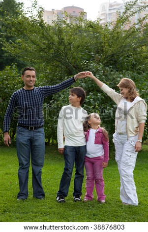 parents playing with children in park, making house, full body - stock photo