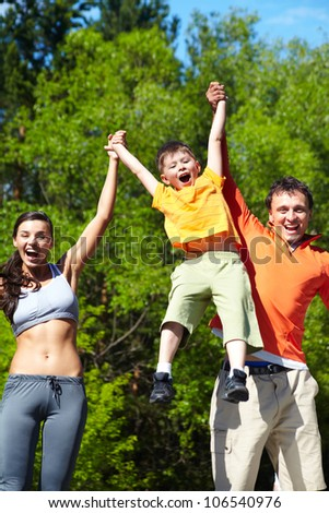 Parents playing with their sun holding him high above the ground - stock photo
