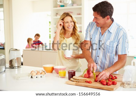 Parents Preparing Family Breakfast In Kitchen - stock photo