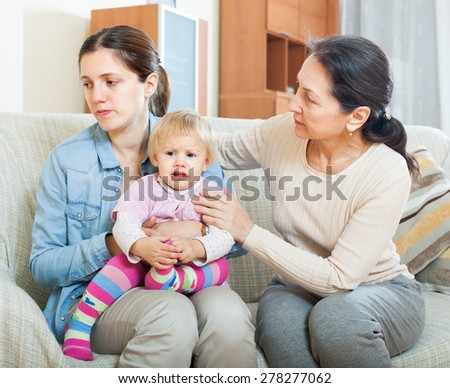 Parents problems. Mature woman comforting adult daughter with baby   at home