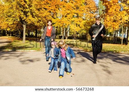 Parents running down their kids in the autumn park - stock photo