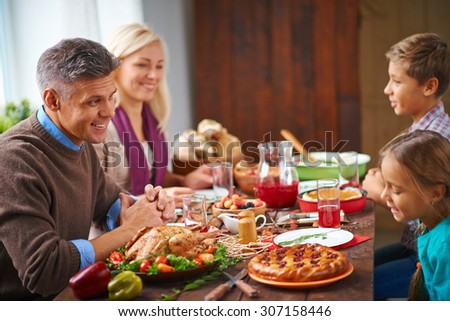Parents sitting at table with their little children - stock photo