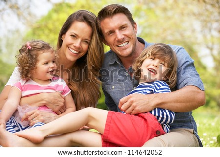 Parents Sitting With Children In Field Of Summer Flowers - stock photo