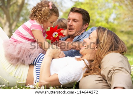 Parents Sitting With Children In Field Of Summer Flowers