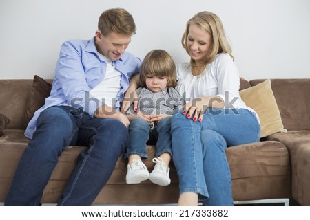 Parents sitting with sad son on sofa at home - stock photo