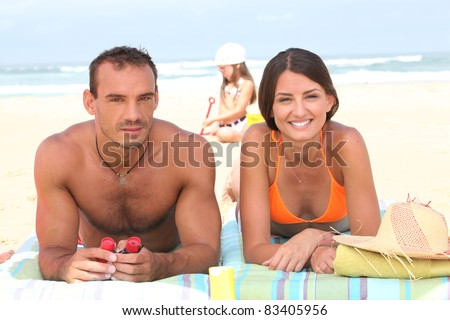 Parents sunbathing as their daughter plays in the sand behind them