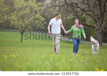 Parents to be  with dog enjoying the green. Picture is toned