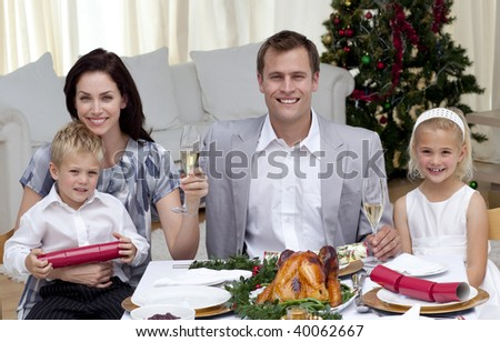 Parents toasting with champagne in Christmas dinner at home - stock photo