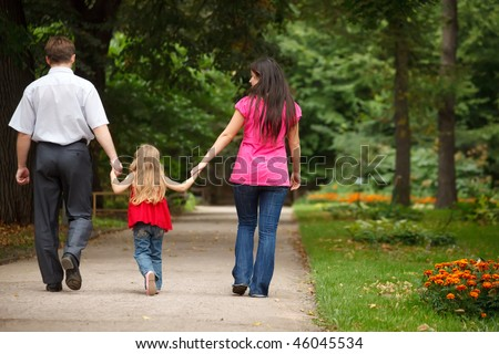 Parents together with daughter walk on summer garden. Leave afar keeping for hands. - stock photo