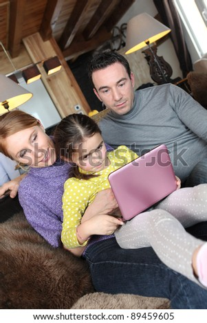 Parents using a pink laptop with their daughter - stock photo