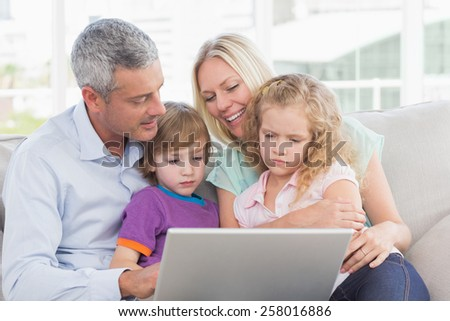 Parents using laptop with son and daughter at home