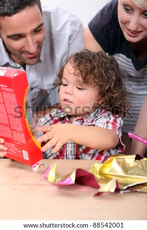 Parents watching their child open a gift - stock photo