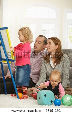 Parents watching toddler girl drawing on board, baby girl playing on floor. - stock photo