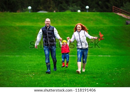parents with a child running - stock photo
