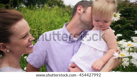 parents with baby holding flowers, smiling and laughing - stock photo