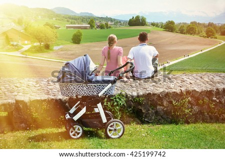 Parents with baby stroller enjoying Alpine panorama. Switzerland - stock photo