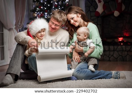 Parents with children are reading wish list for Santa Claus sitting on the floor near the Christmas tree and fireplace - stock photo