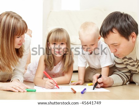 Parents with children drawing laying on a floor
