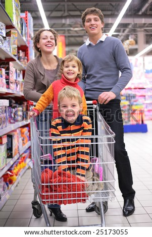 Parents with children in cart in shop, focus on little girl - stock photo