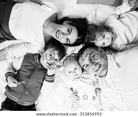 Parents with children lying on bed at home. Happy family concept - stock photo