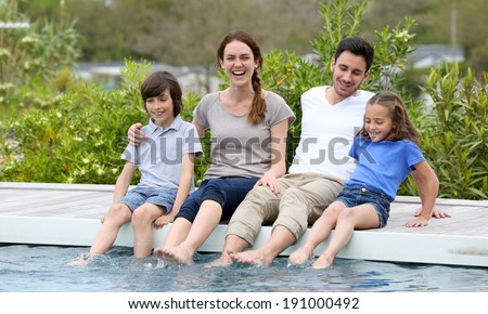 Parents with children relaxing by the pool - stock photo