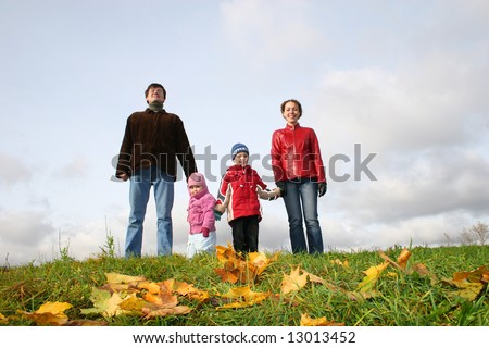 parents with children stand on meadow at autumn