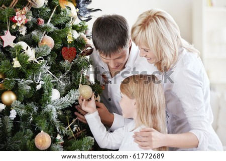 Parents with daughter dress up spruce - stock photo