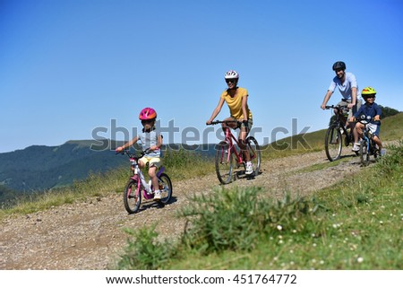 Parents with kids riding bikes in moutain path
