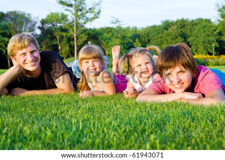 Parents with little daughters  on the green grass - stock photo