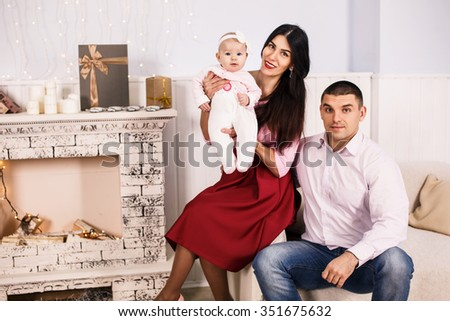 Parents with newborn baby on christmas holiday at home. Happy family concept - stock photo