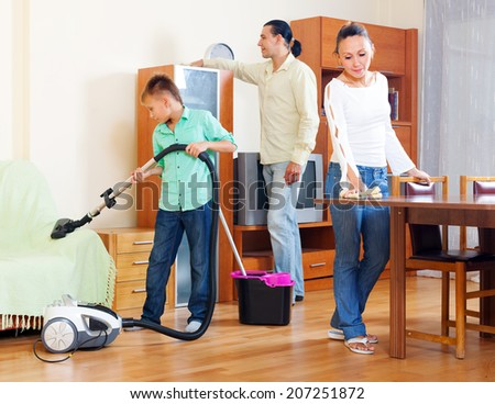 parents with teenage son doing house cleaning  in living room at home - stock photo