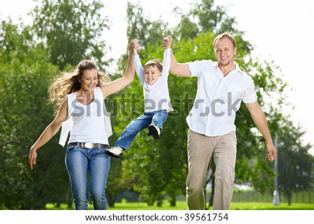 Parents with the small son frolic on the nature - stock photo