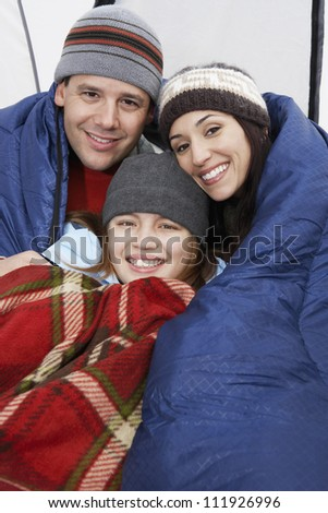 Parents with their daughter relaxing in tent