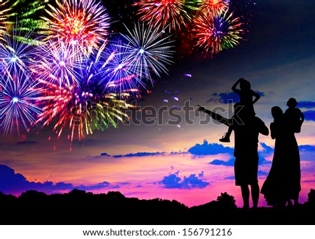 Parents with two children watching fireworks at sunset - stock photo