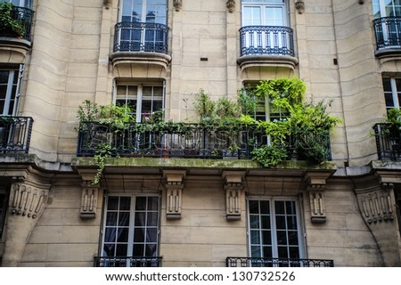 Paris apartment building with vine covered balcony - stock photo