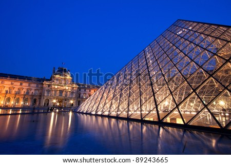 PARIS - APRIL 16: Closeup of Louvre Pyramid shined at dusk on April 16, 2010 in Paris, France. Louvre is the biggest Museum in Paris displayed over 60,000 square meters of exhibition space. - stock photo