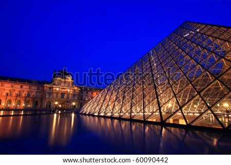 PARIS - APRIL 16: Closeup of Louvre Pyramid shines at dusk during the Summer Exhibition April 16, 2010 in Paris. This is one of the most popular tourist destinations in France. - stock photo