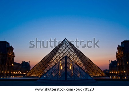 PARIS - APRIL 16: Double of Louvre pyramid shines at dusk during the Summer Exhibition April 16, 2010 in Paris. This is one of the most popular tourist destinations in France. - stock photo