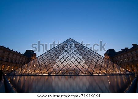 PARIS-APRIL 16: Louvre pyramid at Evening during the Summer Antiquities Exhibition April 16, 2010. Louvre is the biggest Museum in Paris displayed over 60,000 square meters of exhibition space. - stock photo