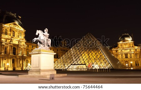 PARIS - APRIL 13: Louvre Pyramid shines at dusk during the Summer Exhibition April 13, 2011 in Paris. Louvre is the biggest Museum in Paris displaying over 60,000 square meters of exhibition space. - stock photo