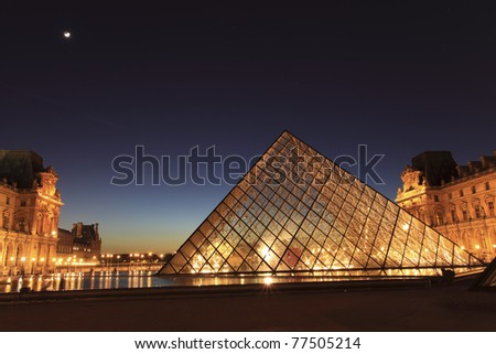 PARIS - APRIL 07: Louvre Pyramid shines at dusk on April 07, 2011 in Paris. Louvre is the biggest Museum in Paris and displays over 60,000 square meters of exhibition space. - stock photo