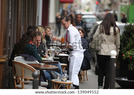 PARIS - APRIL 27 : Parisians and tourist enjoy eat and drinks in cafe sidewalk in Paris, France on April 27, 2013. Paris is one of the most populated metropolitan areas in Europe. - stock photo
