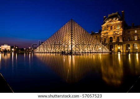 PARIS - APRIL 16: Reflection of Louvre pyramid shines at dusk during the Summer Exhibition April 16, 2010 in Paris. This is one of the most popular tourist destinations in France. - stock photo