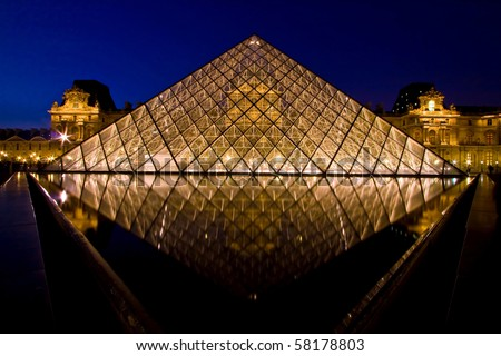 PARIS - APRIL 16: Reflection of Symmetric Louvre pyramid shines at dusk during the Summer Exhibition April 16, 2010 in Paris. This is one of the most popular tourist destinations in France. - stock photo