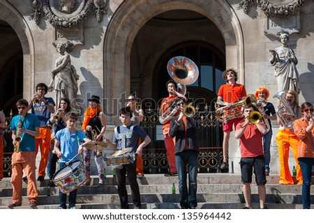 PARIS - APRIL 21: Young brass band near Paris Opera building on April 21, 2013 in Paris, France. Dozens buskers perform on the streets and in metro of Paris. - stock photo
