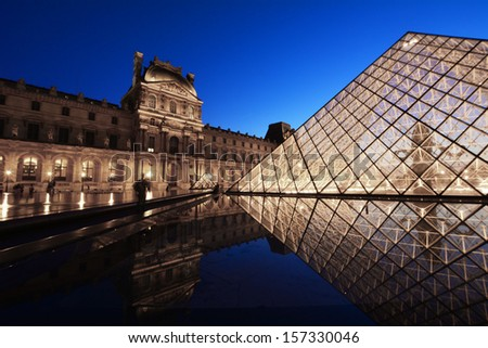 PARIS - AUG 15 : Louvre museum at night in summer on August 15,2013. Louvre museum is one of the world's largest museums with more than 8 million visitors each year. - stock photo