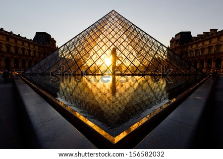 PARIS -AUG 5, 2013      Louvre museum at twilight in summer  AUG 5, 2013 in Paris, France. Louvre Museum is one of the world's largest museums, every year museum visits more than 8 million visitors. - stock photo
