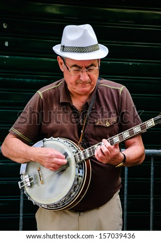 PARIS - AUG 15: Unidentified senior musician plays banjo near Church of Saint-Germain-des-Pres on August 15, 2013 in Paris, France. Dozens buskers perform on the streets and in the metro of Paris.
