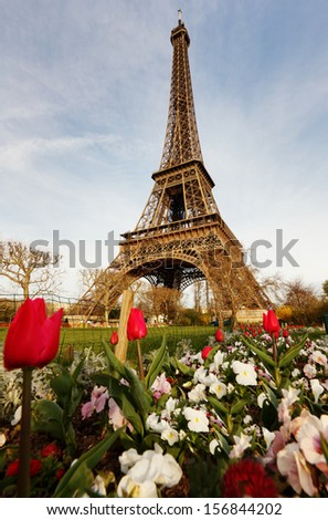 PARIS -  6  AUGUST  13: Illuminated Eiffel Tower at night and people on the Champs de Mars. The popular place for people for romantic evenings - stock photo