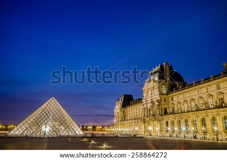 PARIS - AUGUST 18: Louvre museum at sunset on August 18, 2012 in Paris. Annual Summer Exhibition at Louvre. - stock photo